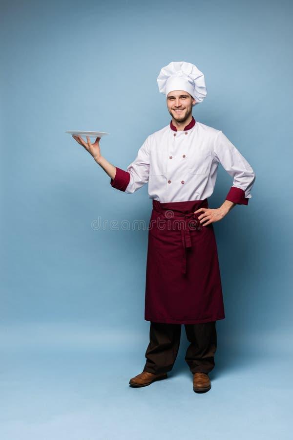 Gelukkige mannelijke chef-kokkok die zich met plaat bevinden die op lichtblauwe achtergrond wordt geïsoleerd royalty-vrije stock foto