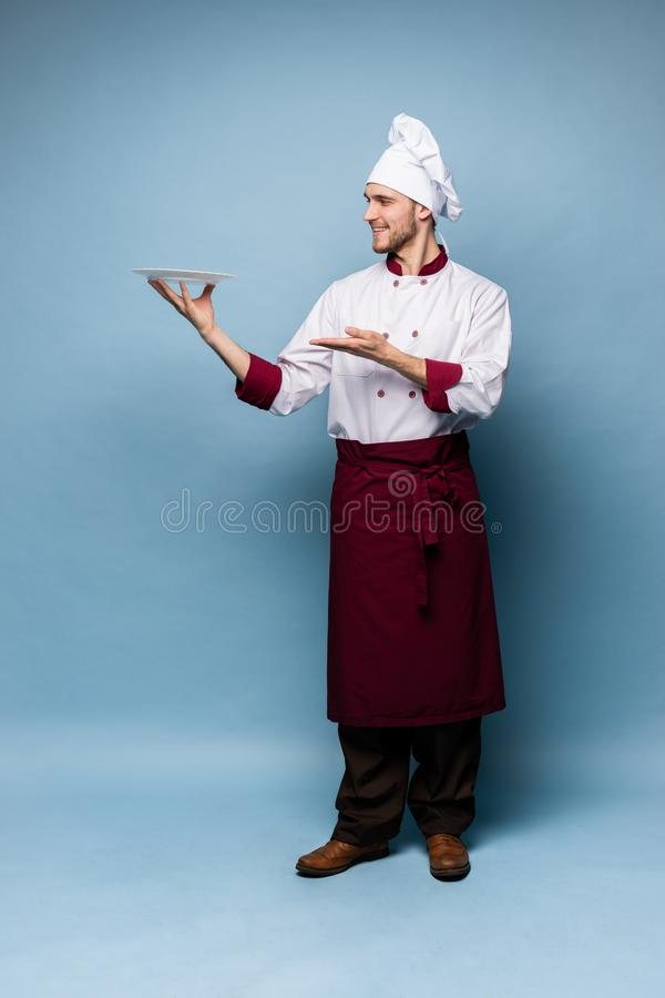 Gelukkige mannelijke chef-kokkok die zich met die plaat bevinden op lichtblauwe achtergrond wordt geïsoleerd royalty-vrije stock afbeeldingen