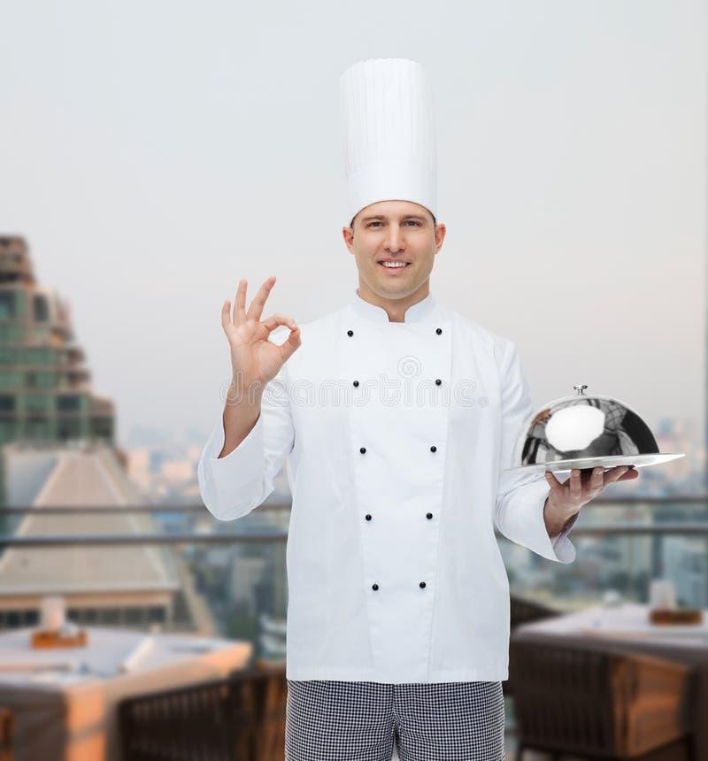 Gelukkige mannelijke chef-kokkok met glazen kap die o.k. teken tonen stock afbeeldingen