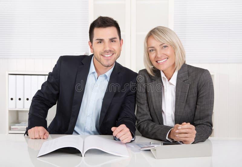 Gelukkige mannelijke en vrouwelijke commerciële teamzitting in het bureau Succe stock afbeelding