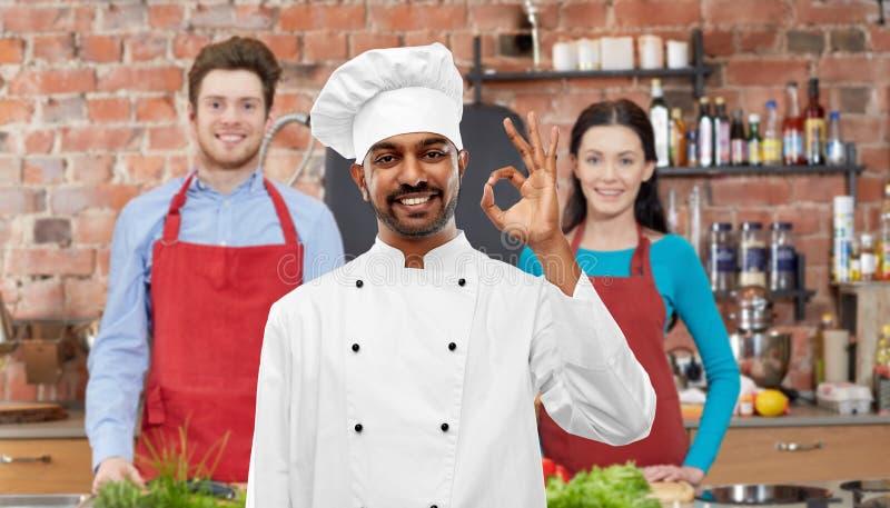 Gelukkige mannelijke Indische chef-kok die o.k. tonen bij het koken van klasse stock fotografie