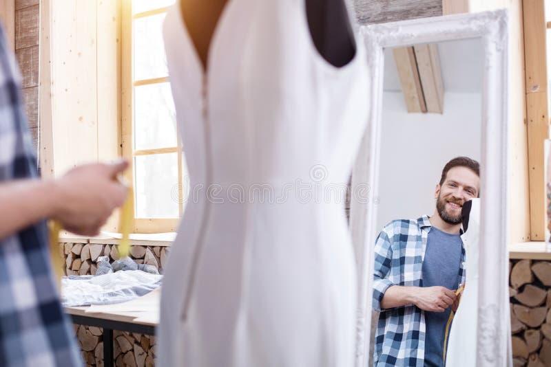 Gelukkige mannelijke meer couturier het bewonderen kleding royalty-vrije stock afbeeldingen