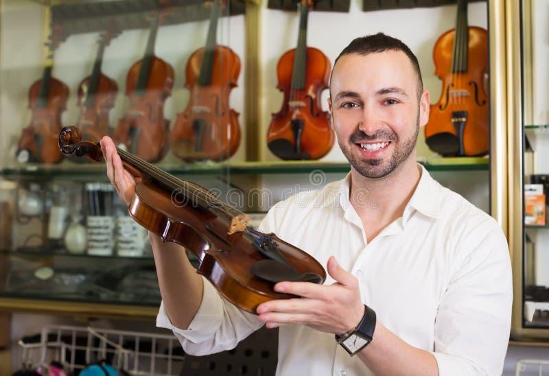 Gelukkige mannelijke musicus die klassieke viool selecteren stock foto's