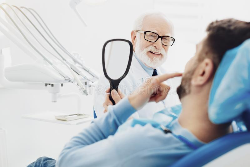 Gelukkige mannelijke patiënt die zijn tanden onderzoeken stock afbeelding