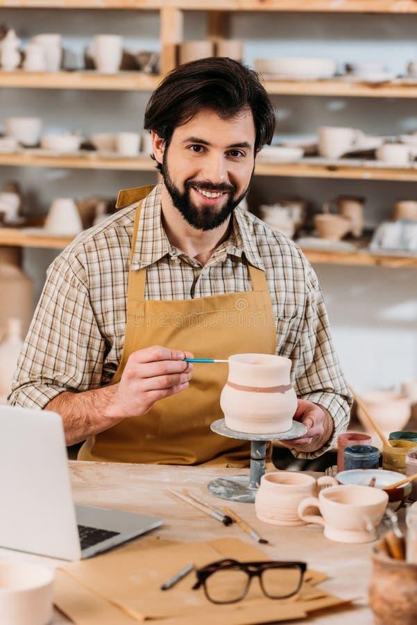 gelukkige mannelijke pottenbakker die ceramische dishware in workshop met laptop schilderen stock fotografie