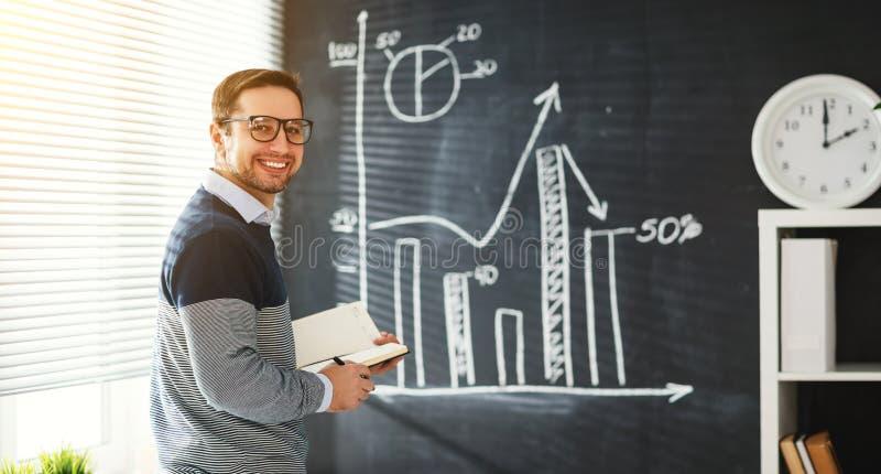 Gelukkige mannelijke student, leraar, freelancer met krijt bij bord stock fotografie
