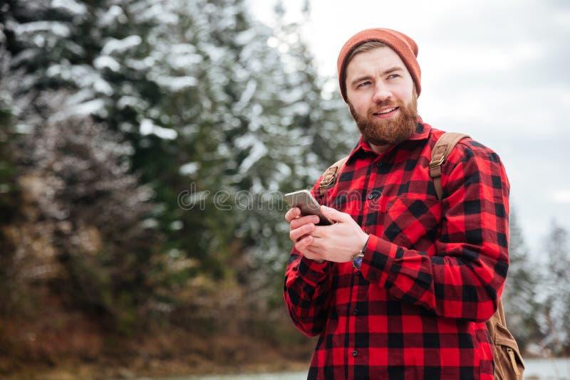Gelukkige mannelijke wandelaar die smartphone gebruiken stock afbeelding