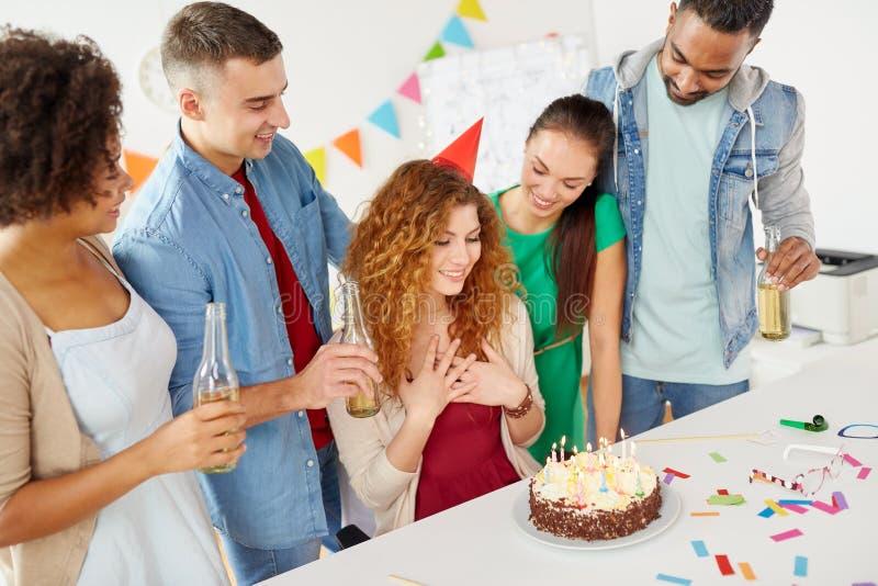 Gelukkige medewerkers met cake bij de partij van de bureauverjaardag royalty-vrije stock afbeeldingen