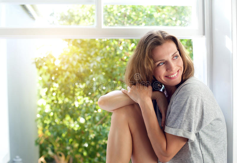 Gelukkige medio volwassen vrouwenzitting door venster thuis royalty-vrije stock fotografie