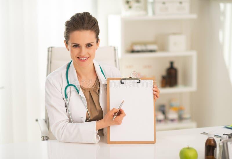 Gelukkige medische artsenvrouw die in klembord richten royalty-vrije stock fotografie