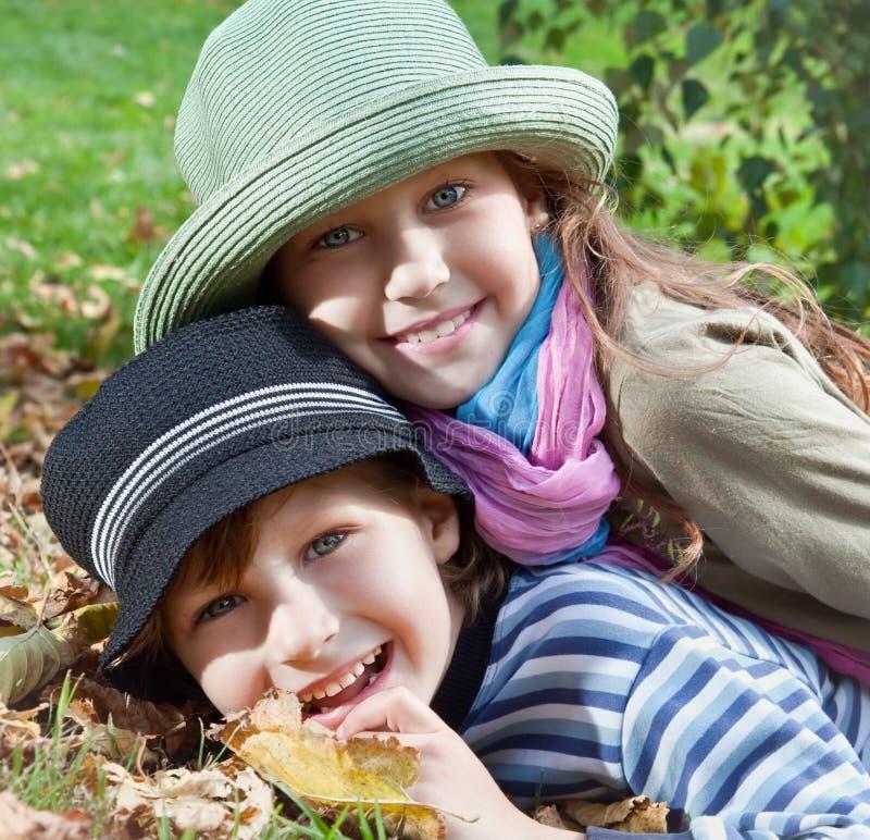 Gelukkige meisje en jongen die de herfst van seizoen genieten stock afbeelding