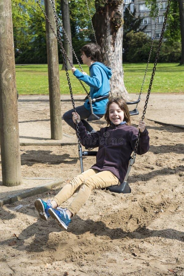 Gelukkige meisje en jongen die op een schommeling slingeren stock foto