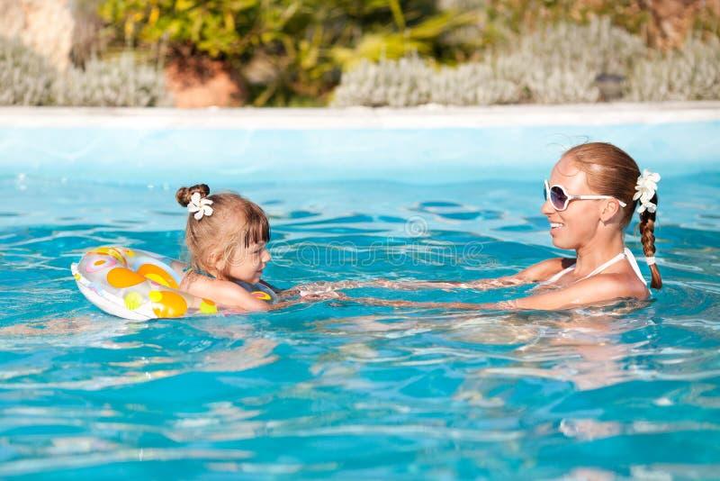 Gelukkige Meisje en Moeder in Pool stock fotografie