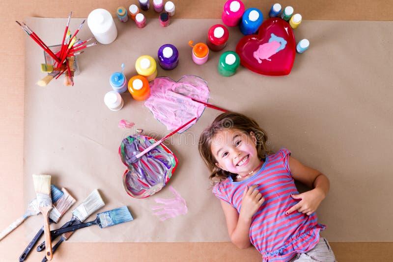 Gelukkige meisjekunstenaar met haar kunstlevering stock foto