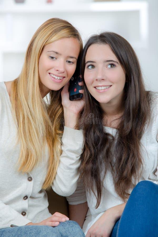 Gelukkige meisjes die aan vrienden op telefoon luisteren stock afbeeldingen