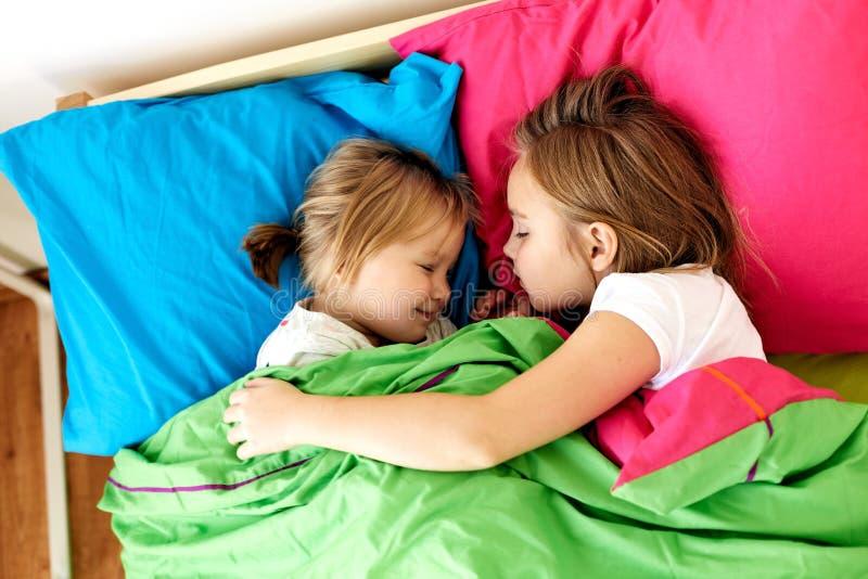 Gelukkige meisjes die in bed thuis slapen royalty-vrije stock foto's