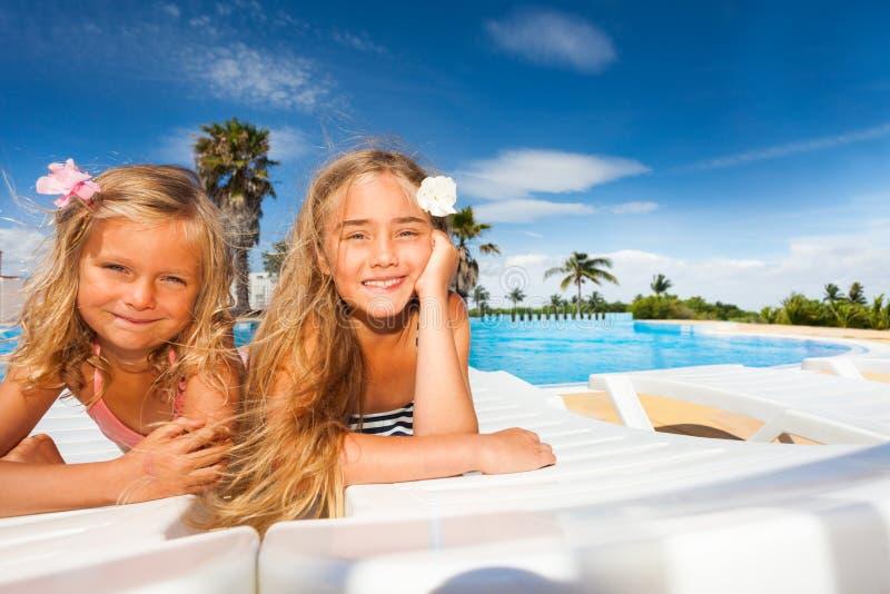 Gelukkige meisjes die door openlucht zwembad zonnebaden stock afbeeldingen