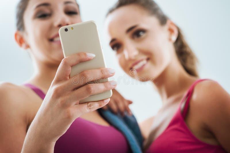 Gelukkige meisjes die een geschiktheid app gebruiken stock foto