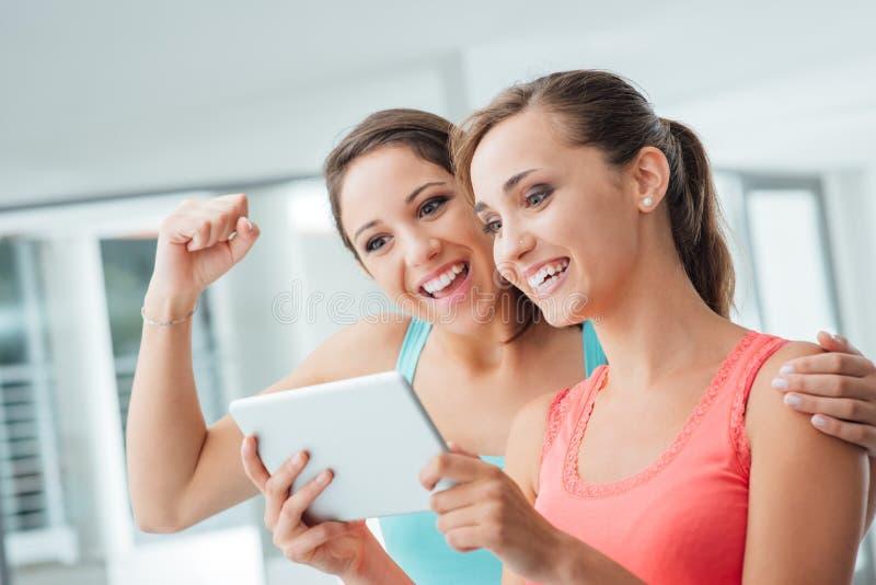 Gelukkige meisjes die een tablet gebruiken stock foto