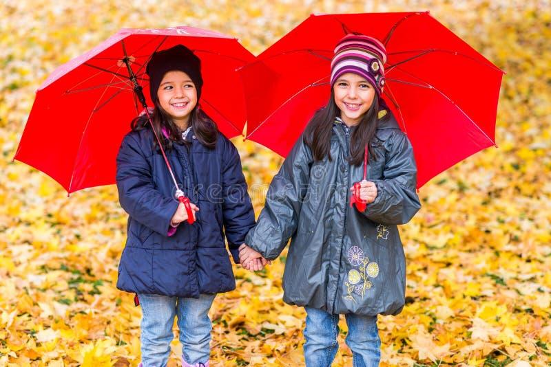 Gelukkige meisjes die met paraplu's in de regen lachen stock afbeelding