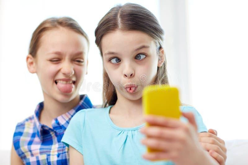 Gelukkige meisjes die met smartphone selfie thuis nemen stock foto