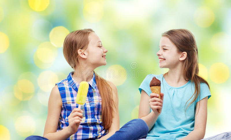 Gelukkige meisjes die roomijs over groen eten royalty-vrije stock foto