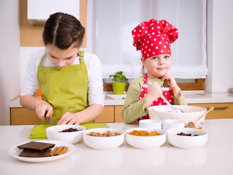 Gelukkige meisjes die samen koken stock foto's