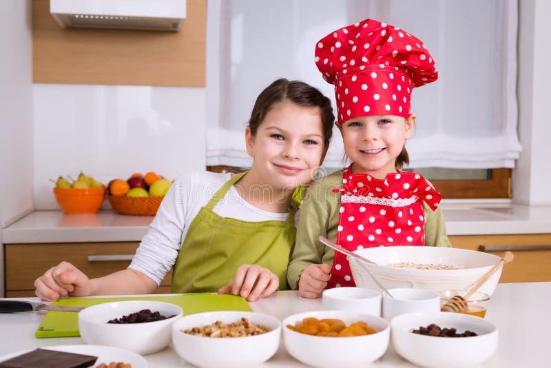 Gelukkige meisjes die samen koken stock afbeeldingen