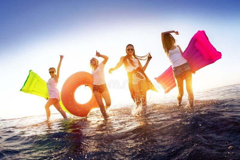 Gelukkige meisjes die in zonsondergangwater lopen met zwemmende matrassen stock fotografie