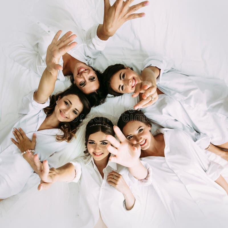 Gelukkige meisjes met een bruid op het witte bed stock foto