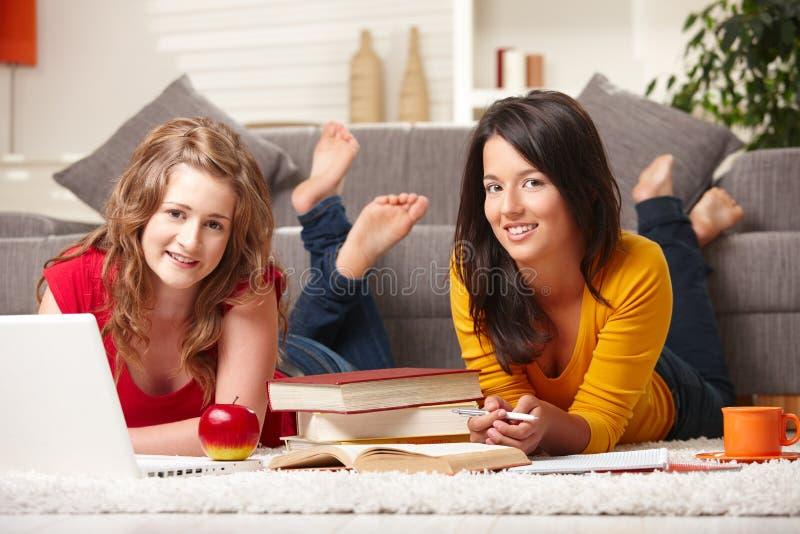 Gelukkige meisjes met laptop en boeken stock afbeeldingen