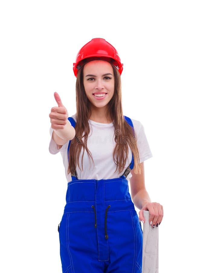 Gelukkige meisjesarbeider in eenvormig en helm die een duim-omhooggaand gebaar tonen Geïsoleerd op wit stock fotografie
