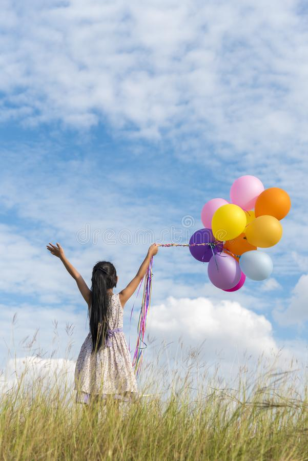 Gelukkige meisjesholding kleurrijk van luchtballons op een groene weide met bewolkte en blauwe hemel stock afbeeldingen