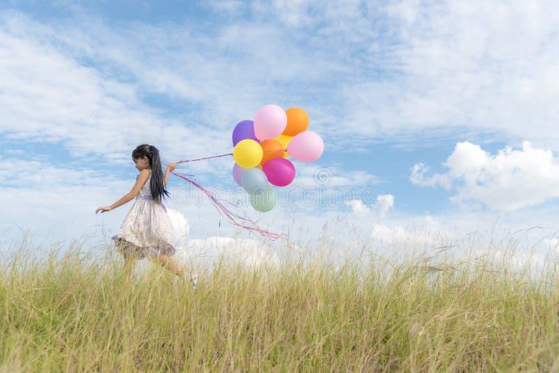 Gelukkige meisjesholding kleurrijk van luchtballons op een groene weide met bewolkte en blauwe hemel royalty-vrije stock foto's