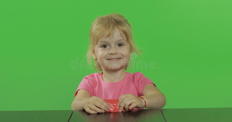 Gelukkige meisjespelen met plasticine op chroma zeer belangrijke achtergrond royalty-vrije stock foto's