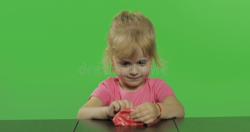 Gelukkige meisjespelen met plasticine op chroma zeer belangrijke achtergrond royalty-vrije stock afbeeldingen