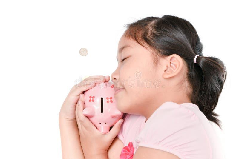 Gelukkige meisjesslaap en het koesteren van roze spaarvarken stock fotografie