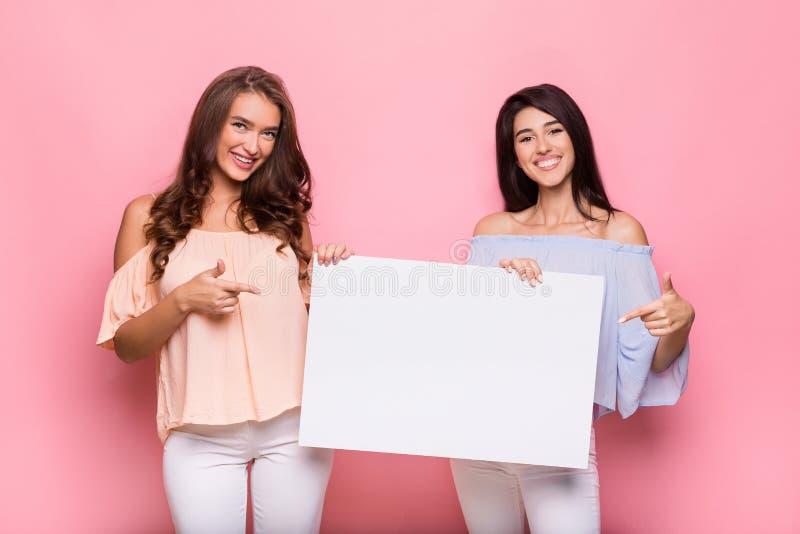 Gelukkige meisjesvrienden die leeg reclamebord houden royalty-vrije stock afbeelding