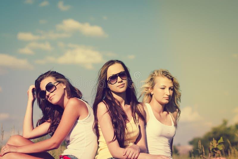 Gelukkige meisjesvrienden op de zomer groene in openlucht achtergrond stock fotografie