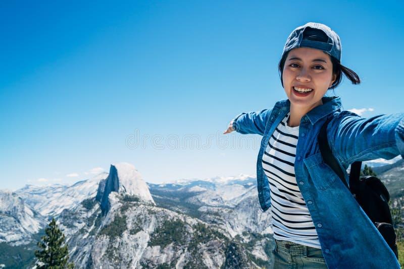 Gelukkige meisjeswandelaar die selfie bovenop berg nemen royalty-vrije stock afbeelding