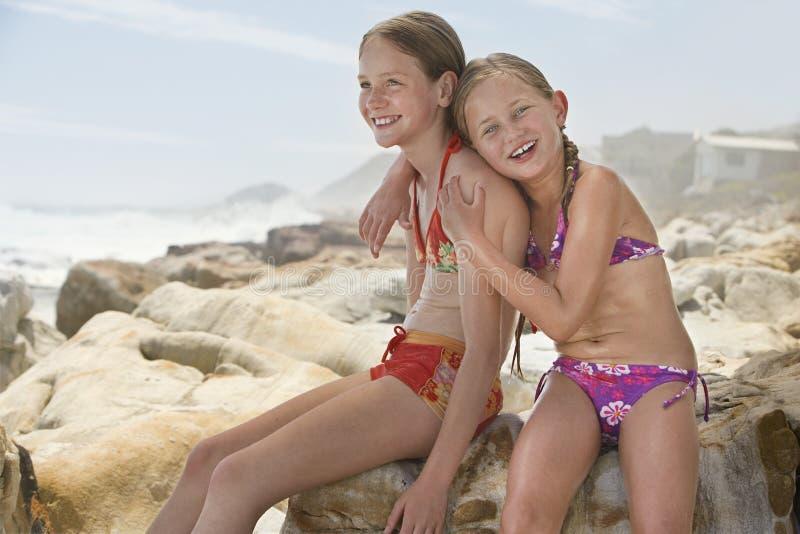 Gelukkige Meisjezitting met Zuster On Rocks stock afbeelding