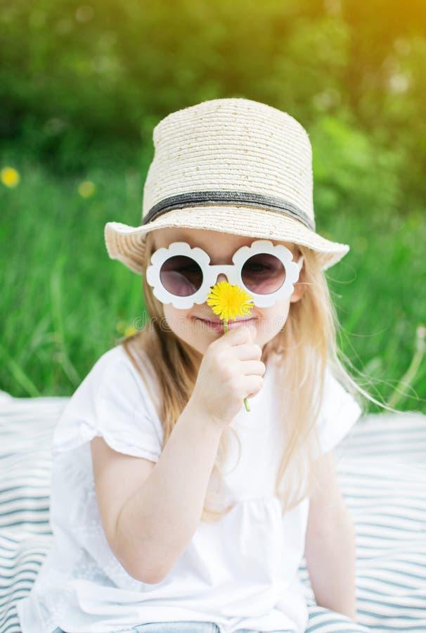 Gelukkige meisjezitting op het groene gras met bloempaardebloem in uw handen stock afbeelding