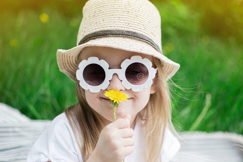 Gelukkige meisjezitting op het groene gras met bloempaardebloem in uw handen stock foto's