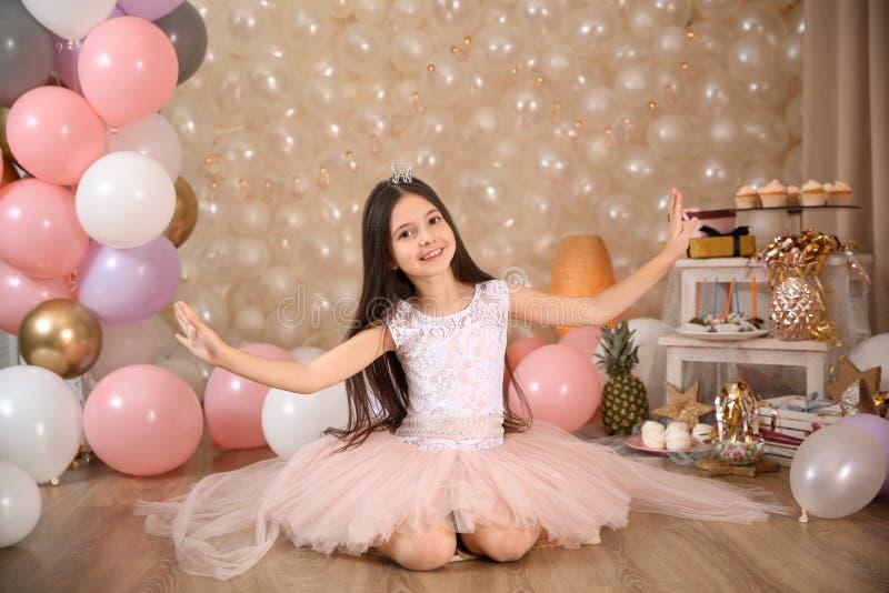 Gelukkige meisjezitting op vloer in prachtig verfraaide ruimte thuis stock afbeeldingen