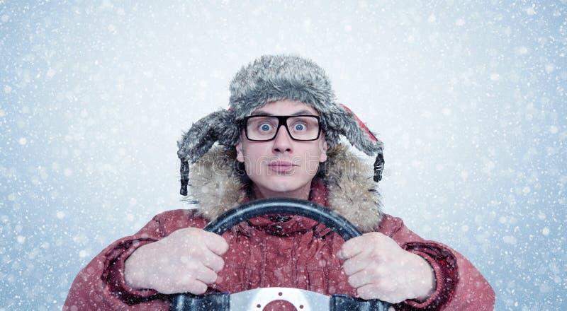 Gelukkige Mens in de winterkleren met een stuurwiel, sneeuwblizzard De bestuurder van de conceptenauto royalty-vrije stock fotografie