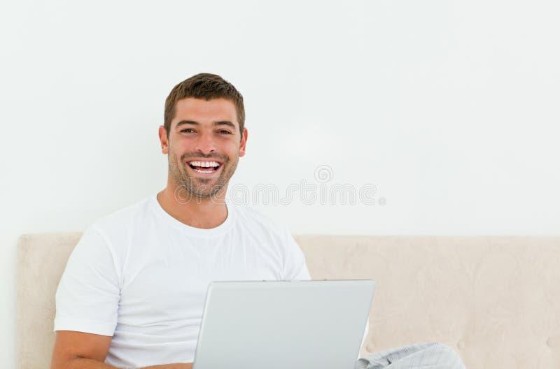 Gelukkige mens die aan zijn laptop in zijn slaapkamer werkt stock afbeeldingen