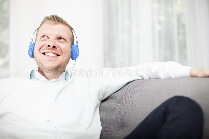 Gelukkige mens die aangezien hij aan zijn muziek luistert glimlachen stock foto's