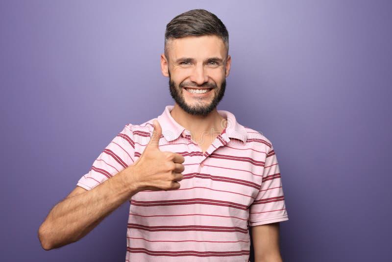 Gelukkige mens die duim-op gebaar op kleurenachtergrond tonen royalty-vrije stock fotografie