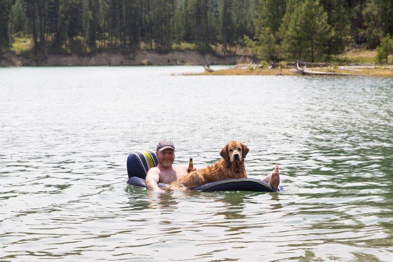 Gelukkige mens die een bier drinken en op een meer met zijn golden retrieverhond drijven stock foto's