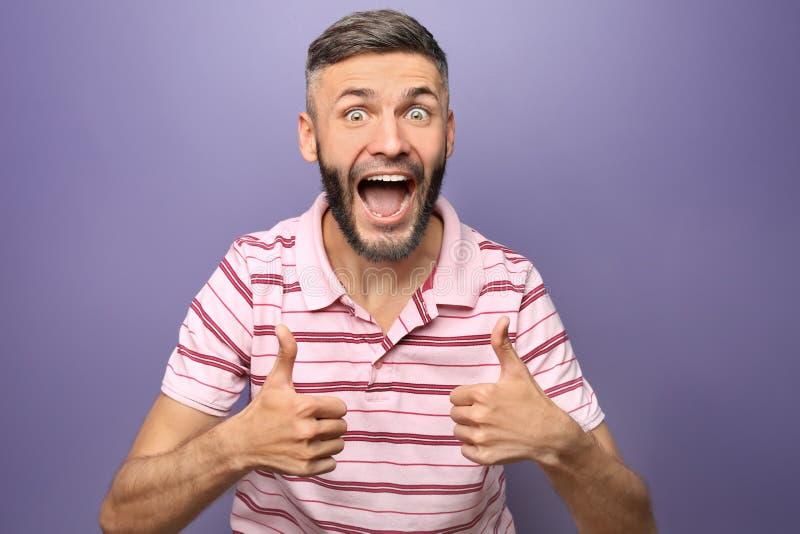 Gelukkige mens die gebaar duim-UPS op kleurenachtergrond tonen stock fotografie